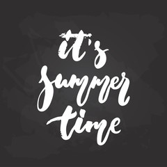 It's summer time - hand drawn seasons holiday lettering phrase isolated on the black chalkboard background. Fun brush ink vector illustration for banners, greeting card, poster design.