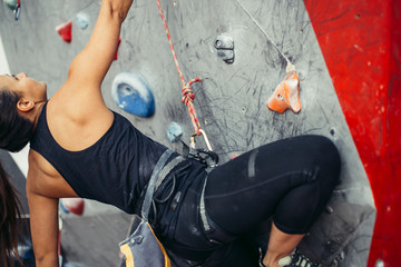 Close up of strong and muscular woman rock climber equipped with a harness and rope for safety exercising on artificial rock.