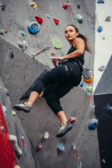 Sporty successful business woman being busy at her hobby-bouldering. Well equipped woman training in a colorful climbing gym, preparing to summer mountain ascend