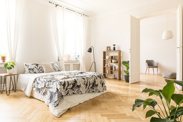 Plant on table next to bed with patterned sheets in white bedroom interior with lamp. Real photo