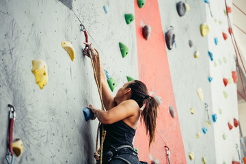 Attractive sporty woman making efforts for a big step up on an artificial colourful wall with handles and hooks.