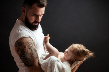 Studio portrait of handsome muscular man in white t-short holding on tatooeed hands cute little baby over black background with copyspace. Family, love and happiness concept.