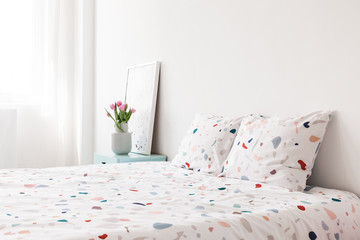 Patterned sheets and cushions on bed in bright bedroom interior with flowers. Real photo