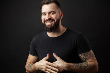 Happy young man. Portrait of handsome young man in casual shirt keeping arms crossed and smiling while standing against black background.