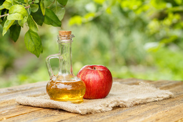 Apple vinegar in glass bottle and fresh red apple on wooden boards with green natural background