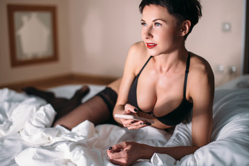 Attractive sexy brunette woman lies on bed in lingerie. Looking aside while chatting by phone.