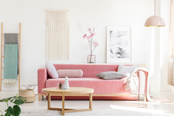 Real photo of a pink sofa with cushions and blanket standing behind a wooden table in bright living room interior with a hanging lamp, ladder, poster and flowers