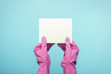 Female hands in pink gloves are holding empty card on a blue background. cleaning service concept. Flat lay, Top view. Copy space.