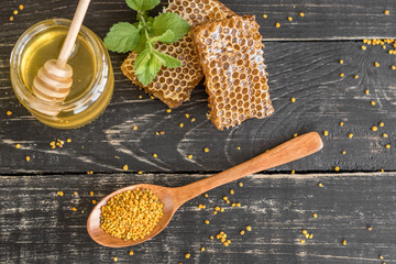 Beautiful transparent honey in bank, honeycombs and pollen on a wooden table. It can be used as a background