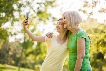 Grandmother and granddaughter are taking selfie in park.