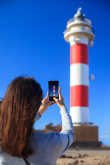 Traveler woman taking photo of lighthouse on beach on Canary Islands, Spain