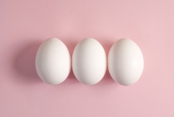 Group of three white eggs on a pink background