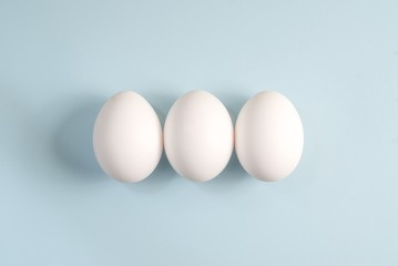 Three white eggs on a blue background