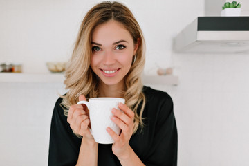 Happy beautiful caucasian blond woman in sleepwear drinks coffee in the kitchen and smiles at camera at home woke up in the morning on a sunny day.