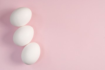 Fotobehang Group of three white eggs on a pink background