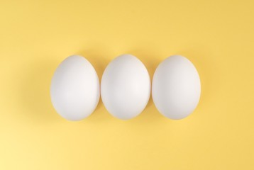 Three white eggs on a yellow background