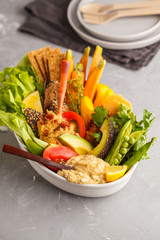 Vegetarian Arabic dip hummus with vegetables and different snacks on a light background. Healthy vegan food concept.