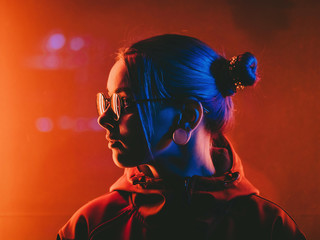 Millennial pretty girl with unusual hairstyle near glowing red neon of city at night. Dyed blue hair in braids. Mysterious hipster teenager in glasses. Reflection of light.