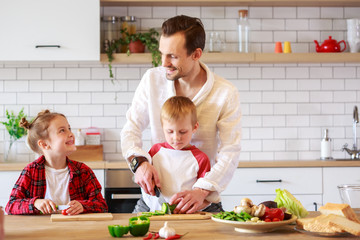 Picture of father with daughter and son cooking at table