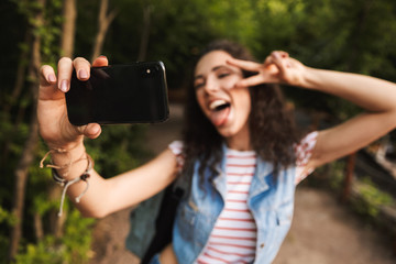 Blurry image of brunette teenage woman 18-20 showing peace sign and screaming with tongue out while taking selfie photo in green park on smartphone in focus