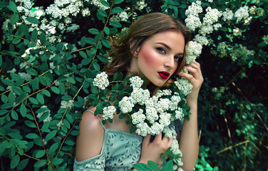 Among the flowering bushes sits a beautiful young girl. White flowers. Spring. Girl with hair in blue dress. Portrait. Romance.