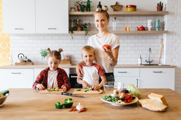 Photo of young mother with daughter and son cutting vegetables at table