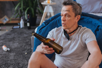 Recollections about party. Weary mature man looking aside and holding bottle
