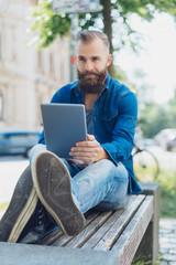 mann mit bart sitzt in der stadt und schaut auf sein tablet