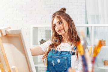 Pretty talented female painter painting on easel