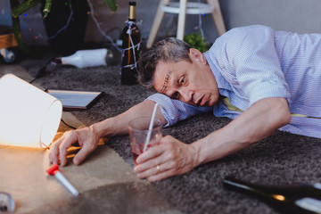 Uncontrollable desire. Gloomy mature man locating on floor and desiring cocktail
