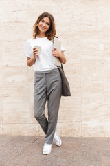 Full length image of beautiful modern woman standing against beige wall outdoor with silver laptop, and takeaway coffee in hands