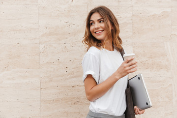 Image of joyful european woman walking against beige wall outdoor with silver laptop, and takeaway coffee in hands