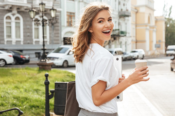 Photo of pretty european woman walking through city street with silver laptop, and takeaway coffee in hands