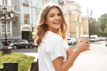 Portrait of smiling european woman strolling through city street with silver laptop, and takeaway coffee in hands
