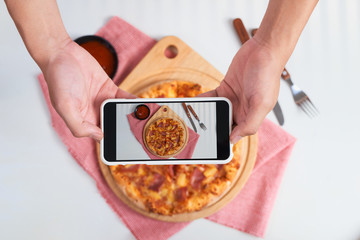 Hand making shot on mobile phone: pizza with pineapple, prosciutto and mozzarella cheese on wooden serving board over light red backdrop. Top view. Selective focus