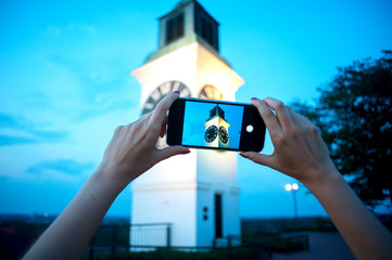 Female hands holding smart phone and taking a picture of an old clock tower.