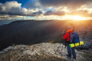 Photographer takes pictures on top of the mountain in autumn. Traveler with backpack enjoying a view from the mountain top at sunset
