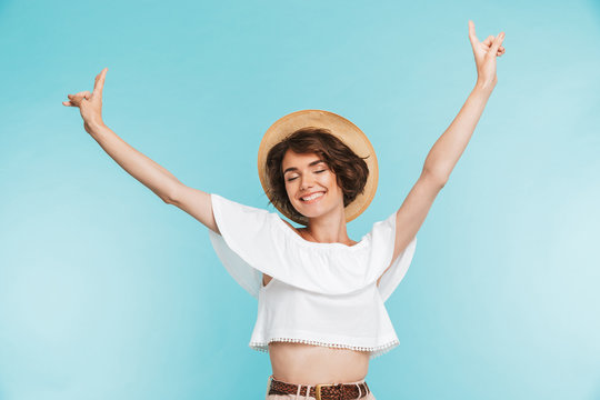 Portrait of a cheerful young woman in summer hat