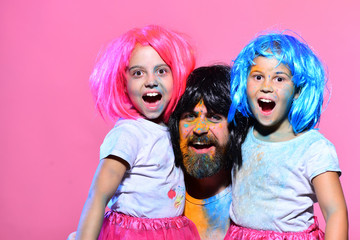 Schoolgirls and man with beard have paint spots on faces