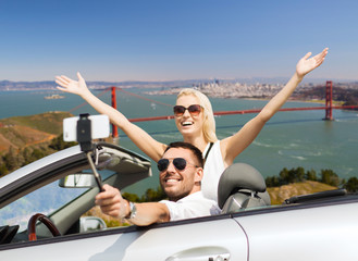 road trip, technology and travel concept - happy couple driving in convertible car and taking picture by smartphone on selfie stick over golden gate bridge in san francisco bay background