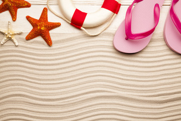 Summer beach background - flip flop, lifebuoy and starfish on beach sand and wooden plank