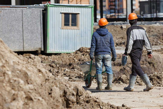 Two workers in helmets are driven a wheelbarrow on the background of a building shed.