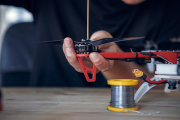 Photo of man with screwdriver cleaning quadrocopter
