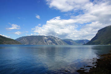 Landscape on the fjord in Norway from the seashore, the mountain on the other side, blue clear water