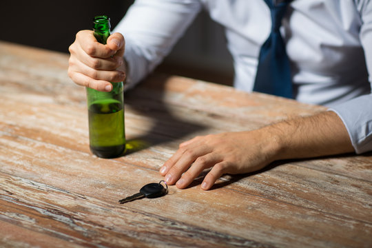 alcohol abuse, drunk driving and people concept - close up of male driver hands with beer bottle and car key on table