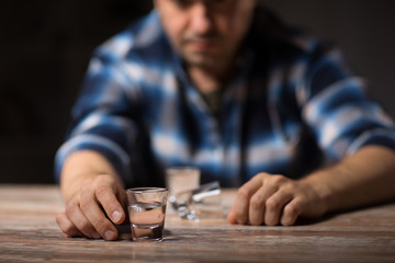 alcoholism, alcohol addiction and people concept - male alcoholic drinking shot at night