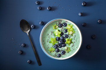 healthy spirulina smoothie bowl with blueberry, kiwi stars, chia seed