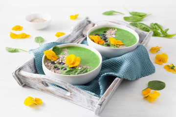 green spinach smoothie bowl with blueberry, chia seed and edible pansy flowers
