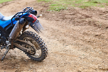 Single offroad mountain motorcycle or bike taking part in motocros competition parked on dirty terrain road
