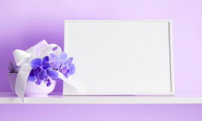 Photo frame mock up, beautiful flowers bouquet on the shelf, gift with white satin bow, lilac orchid on violet wall background.